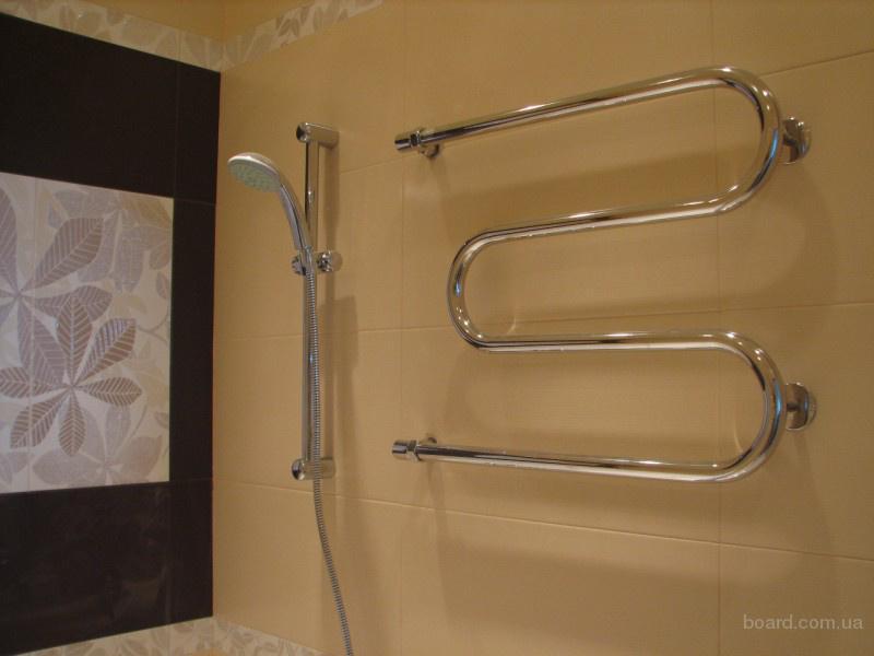 Зигзагообразный полотенцесушитель (хромированный) установленный в ванной комнате, выложенной керамической...